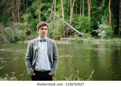 The portrait of attractive groom in a suit and bow tie with boutonniere or buttonhole on jacket, is standing against the background of the forest at nature near river or lake.