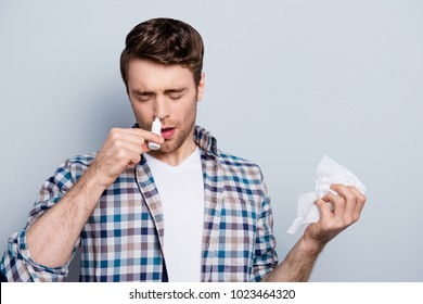 Portrait of attractive guy with a nasal spray and tissue in hands, using nose drops over grey background, concept of treatment for allergies or the common cold, winter style