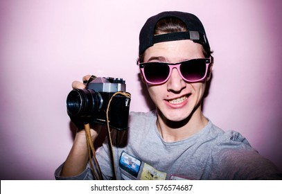 Portrait of the attractive guy with retro camera on the pink background