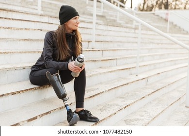 Portrait of attractive handicapped woman in black tracksuit with prosthetic leg sitting at the street stairs and holding thermos cup