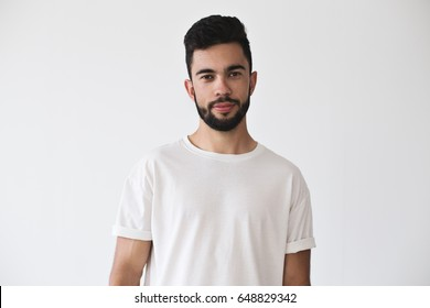 Portrait of attractive handsome young millennial with beard who looks into camera on isolated simple background and wears white t-shirt from premium organic materials