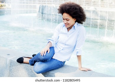 Portrait of Attractive Happy Afro American Young Woman wearing blue jeans, mixed race female relaxing near water fountain