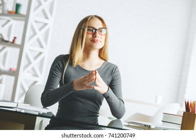Portrait of attractive happy businesswoman sitting at glass office desk with supplies and other items. Occupation, workplace concept