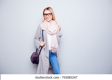 Portrait of attractive happy careless young woman with beaming smile is wearing warm cardigan, scarf and holding her purple handbag. She is isolated on grey background
