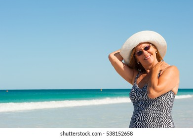 Portrait attractive happy relaxed mature woman with white summer hat at beach, ocean, horizon and blue sky as background.