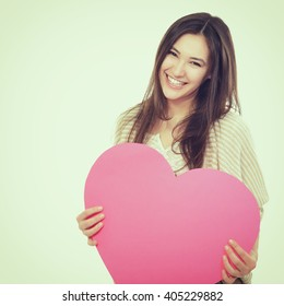 portrait of attractive happy smiling teen girl with pink heart, love holiday valentine symbol. Image toned and noise added.