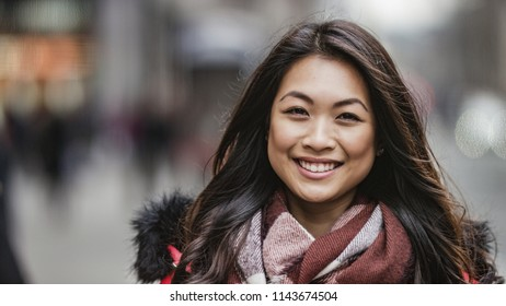 Portrait of attractive and happy smiling young Asian woman looking to camera on the street