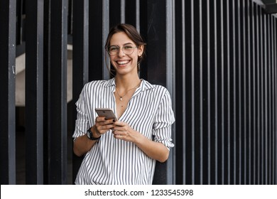 Portrait of attractive happy spanish woman holding smartphone next to urban wall at the city street. Business concept, creative worker, break, walking street, official clothes, stylish and succesfull