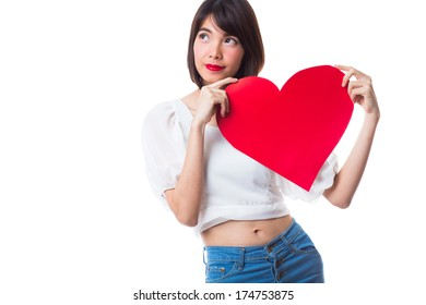 Portrait of attractive happy woman holding heart and looking up to copy- space