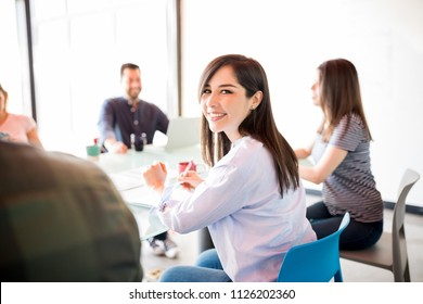 Portrait of attractive hispanic business woman sitting with coworkers in meeting room