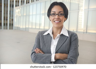 Portrait of an attractive Hispanic business woman with her arms folded standing in an outdoor business environment