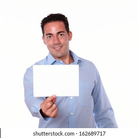 Portrait of an attractive hispanic guy holding a white card while standing and smiling at you on isolated background - copyspace