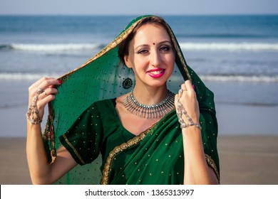portrait of attractive indian female model in vacation on paradise tropical beach ocean sea. hindu woman with kundan jewelry set traditional India costume sari.asian girl sensual look bindi tikka