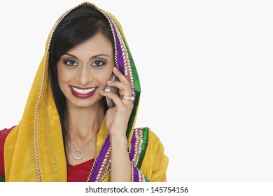 Portrait of an attractive Indian woman in traditional wear answering phone call over white background