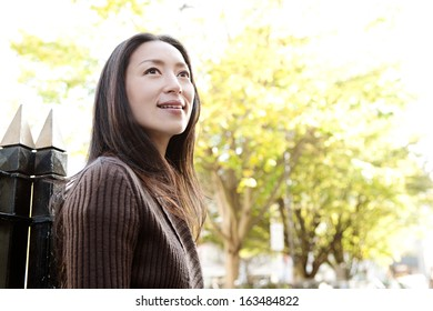 Portrait of an attractive Japanese tourist woman visiting the city of London during a sunny day and standing near a park with black railings, smiling and looking away while turning, outdoors.