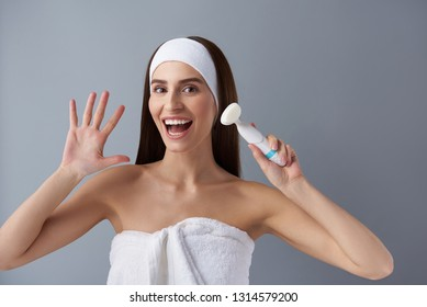 Portrait of attractive joyful girl with wide open mouth demonstrating electric brush cleanser. She wearing soft bath towel and headband