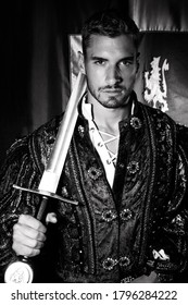 Portrait of attractive king with beard dressed in costume holding a sword and looking at camera