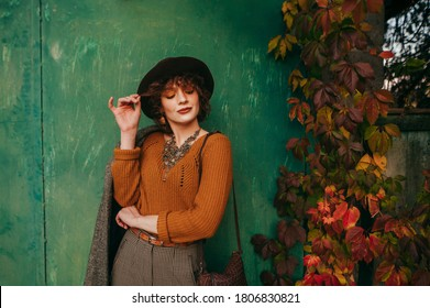 portrait of attractive lady in vintage clothes against green grunge autumn wall background,looking down and to the side and smiling. Photo of attractive woma from village on grunge background.
