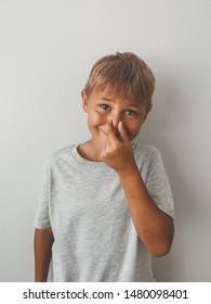 Portrait attractive latino boy making bad smell sign. Beautiful human face expression and emotions. Child pinching his nose, on gray background.