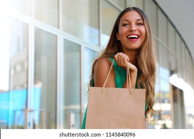 Portrait of attractive laughing woman with shopper bag in her hand with flare. Beauty fashion smiling girl doing shopping. Let's go shopping concept. Copy space.