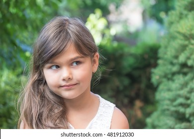 Portrait of attractive little girl with long hair outdoors. Girl peeks top left.