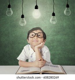 Portrait of an attractive little student with a round glasses and a book, looking up at the bright lamp