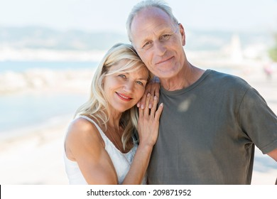 Portrait of an attractive loving middle-aged couple posing close together at the beach smiling at the camera