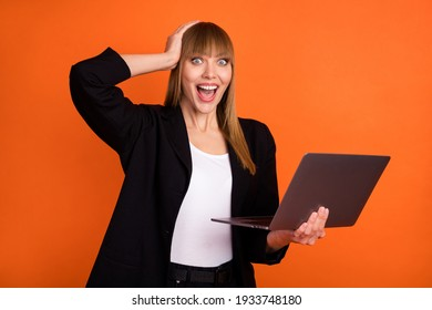 Portrait of attractive lucky cheerful girl specialist using laptop great news reaction isolated over bright orange color background