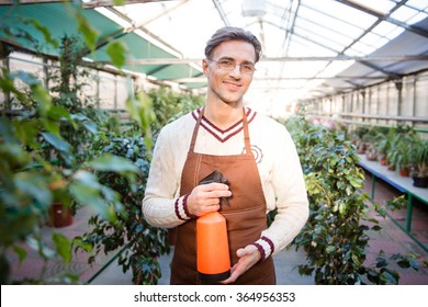 Portrait of attractive male gardener in glasses standing and holding water pulveriser in greenhouse