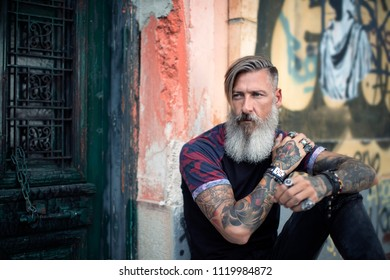 Portrait of an attractive man with a beard and tattoos sitting on a wall