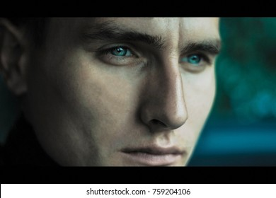 Portrait of attractive man with bright blue eyes thinking of something very seriously