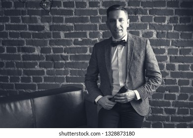 portrait of an attractive man with a microphone in his hands and in a suit against a brick wall