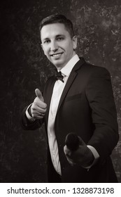 portrait of an attractive man with a microphone in his hands and in a suit