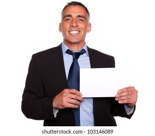 Portrait of a attractive man on suit smiling and holding a white card with copyspace on isolated background