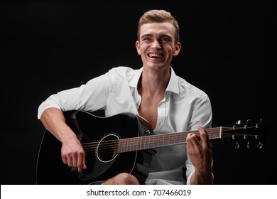 A portrait of an attractive man playing on a dark guitar and singing songs on a saturated black background. A handsome young boy in white blouse practicing in playing guitar. Art concept.