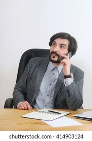 portrait of attractive man speaking on his mobile at his desk in the office; business concept