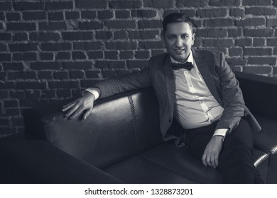 portrait of attractive man in suit on brick wall background