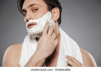 Portrait of attractive man with towel on neck putting shaving foam on face while having morning skincare isolated over gray backgroung