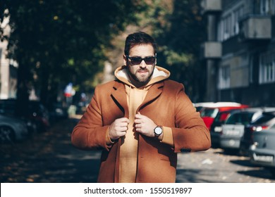 portrait of attractive man wearing sunglasses, brown coat and a leather watch. street style city portrait 2019