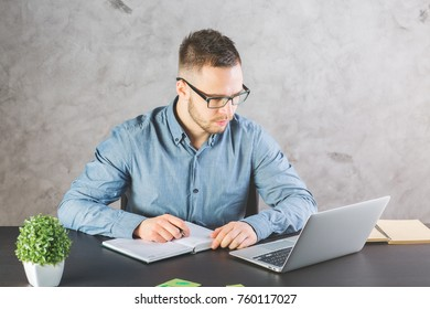 Portrait of attractive man working on project in modern office. Occupation, work, online education and lifestyle concept.