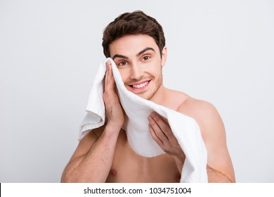 Portrait of attractive, manly, naked macho wiping his face with towel after peeling, mask, moistening, isolated on white background, making every morning procedure, looking at camera