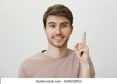 Portrait of attractive mature caucasian guy with pretty face raising index finger and pointing up or showing number one, smiling broadly, having great idea and wanting to share it with boss