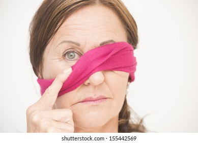 Portrait attractive mature woman with blindfold covering one eye and sad concerned look, isolated on white background.