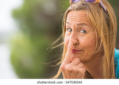Portrait attractive mature woman with funny happy friendly relaxed smile, poking nose with finger, blurred background, outdoor copy space.