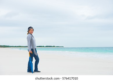 Portrait attractive mature woman happy, relaxed and friendly with umbrella at beach on cold cloudy day, blurred background, copy space.