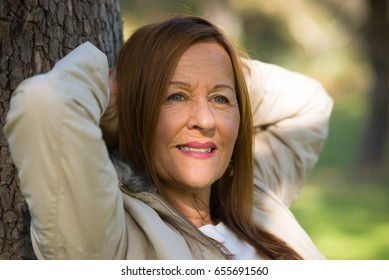 Portrait attractive mature woman with long hair posing happy relaxed, thoughtful and confident outdoors in park, friendly smiling.