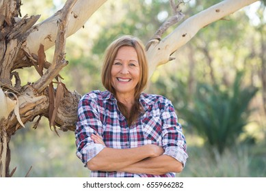 Portrait attractive mature woman in rural country, wearing plaid shirt, posing relaxed with happy smile against Australian outback bush background.