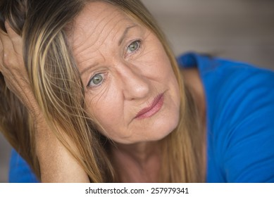 Portrait attractive mature woman with sad, lonely, depressed and stressed facial expression, worried, blurred background.