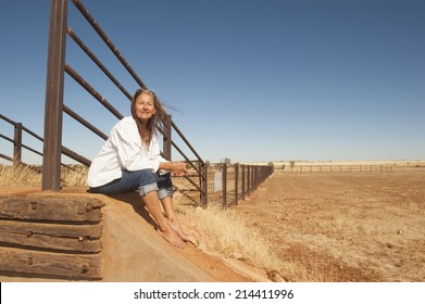 Portrait attractive mature woman sitting relaxed smiling at metal fence line in rural farming area in outback Australia, with dry arid agricultural country and blue sky as background and copy space.