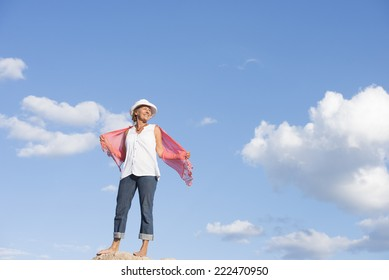 Portrait attractive mature woman standing happy relaxed smiling outdoor on top of mountain or rock, posing in hat and jeans, blue sky as background and copy space.